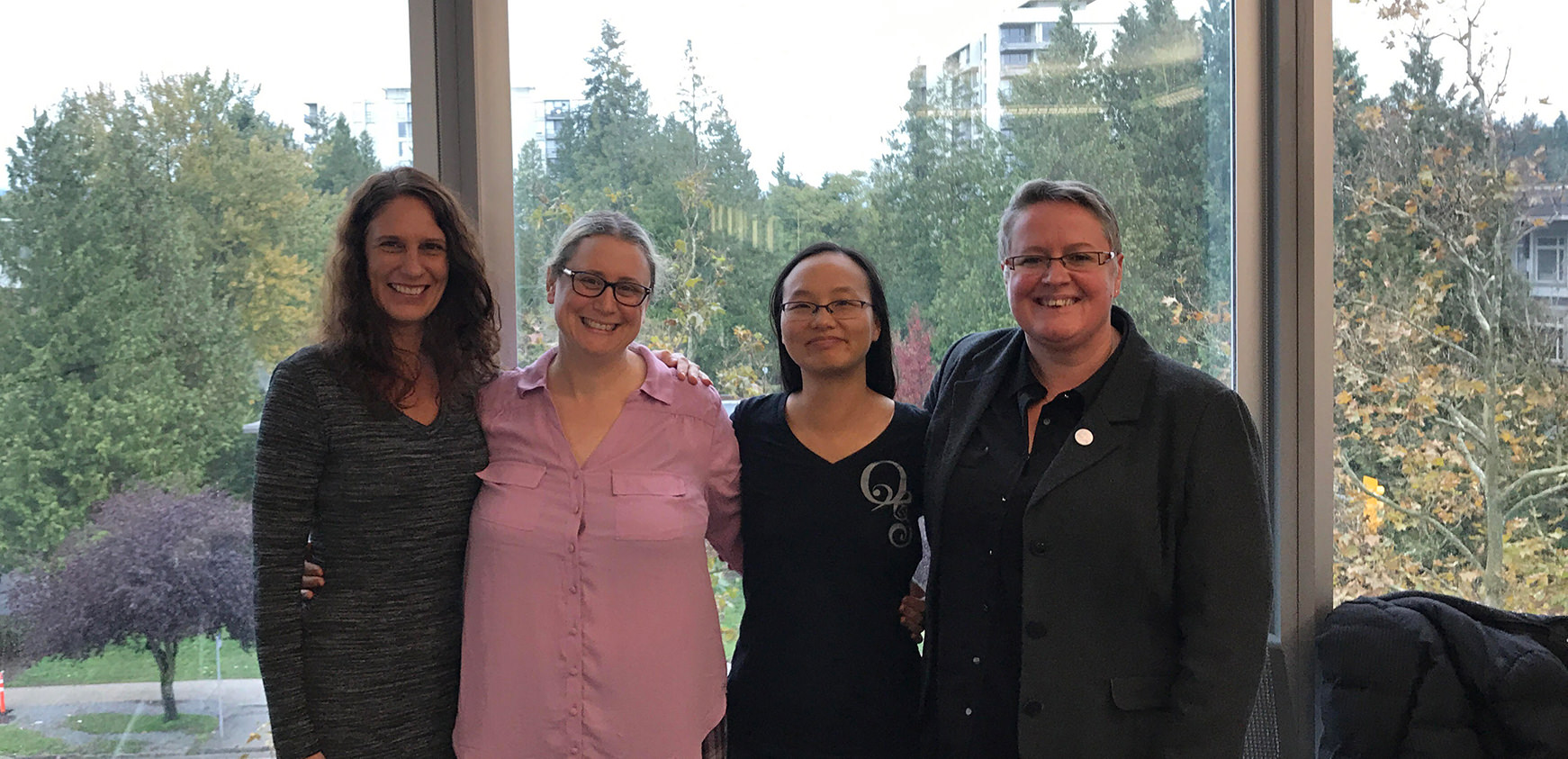 Photo of: Dr. Erin Michalak, Dr. Michelle Walks, Dr. Iva Cheung, and Beverley Pomeroy, standing together in front of a window.
