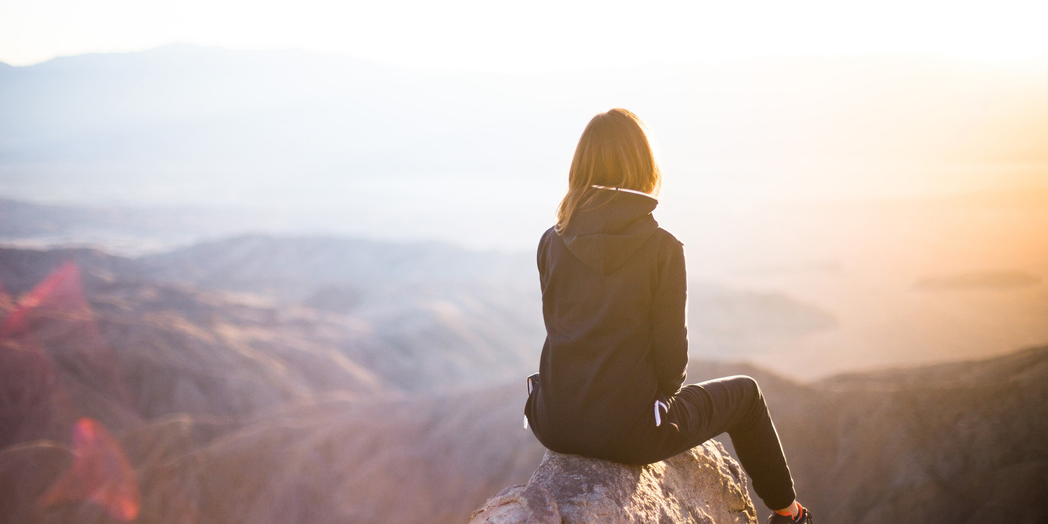 Image of woman looking out from the top of a mountain, for article about quality of life and the Bipolar Wellness Centre.
