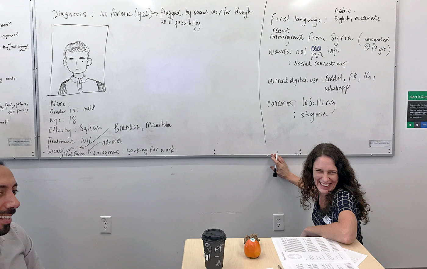 Erin does some whiteboarding while Aidin smiles. She's filling out a persona template for an 18-year old Syrian immigrant.