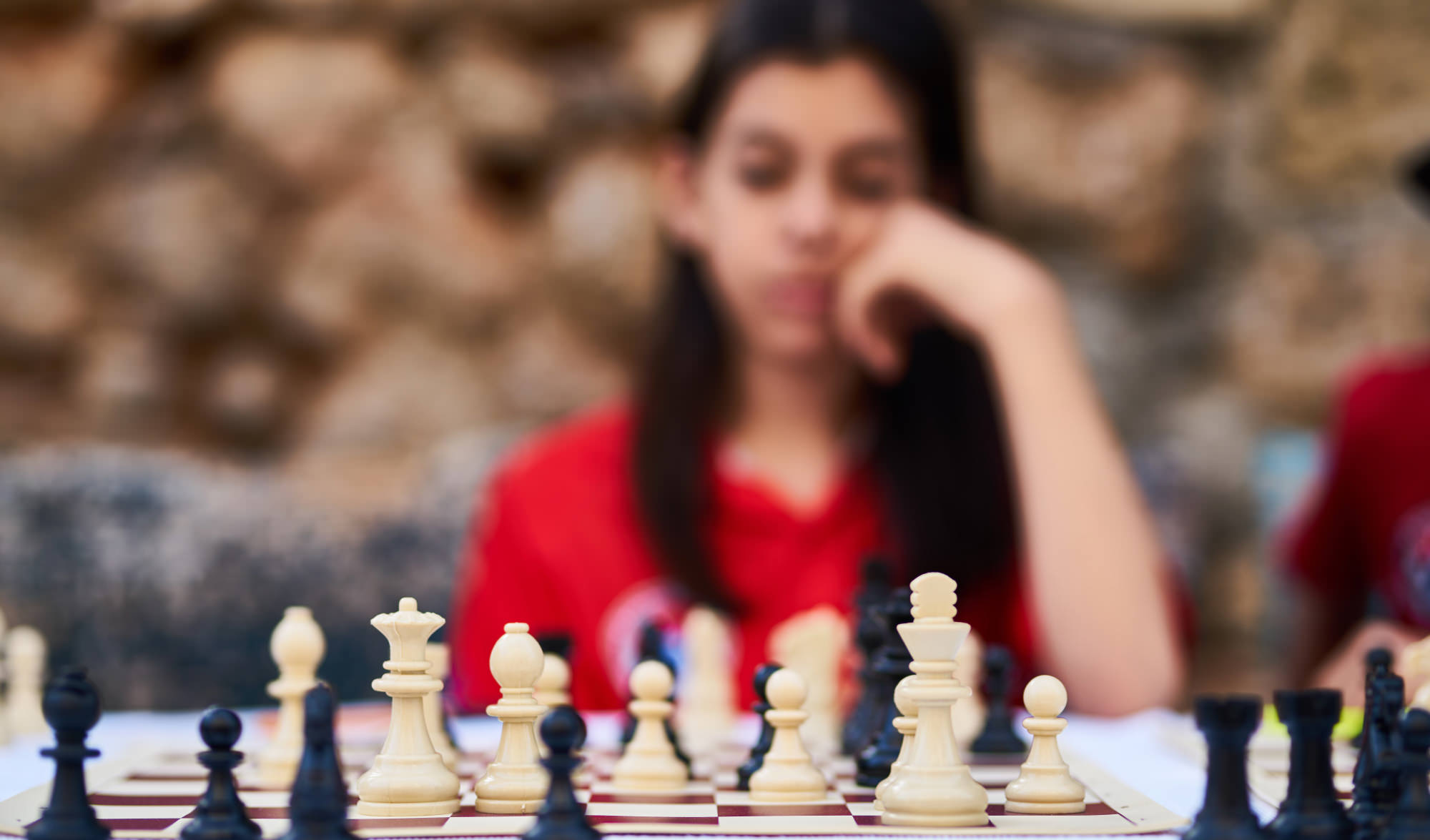 A woman pondering what move to make during a chess game, meant to represent cognition and possible bipolar brain damage.