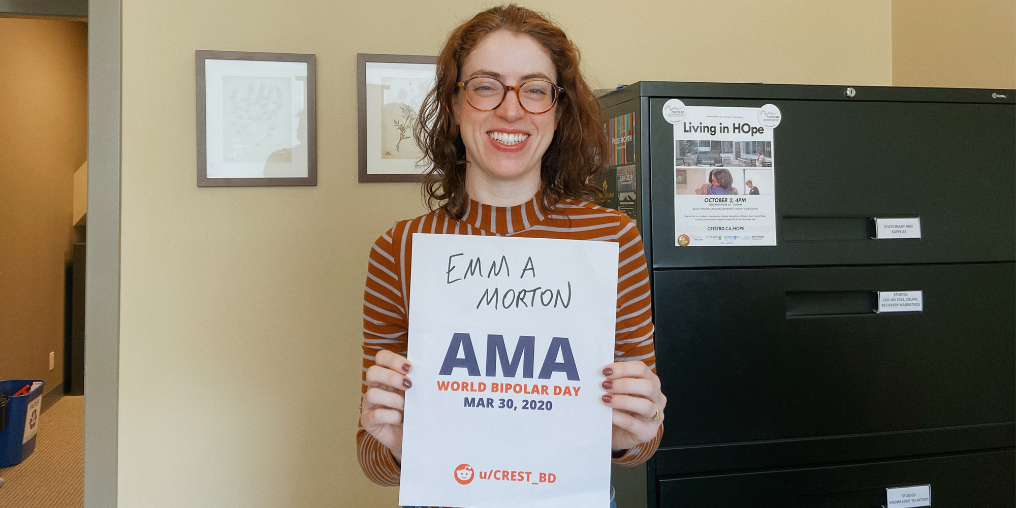 Emma in her office, smiling and holding a sign proving she will be involved in the bipolar ama.