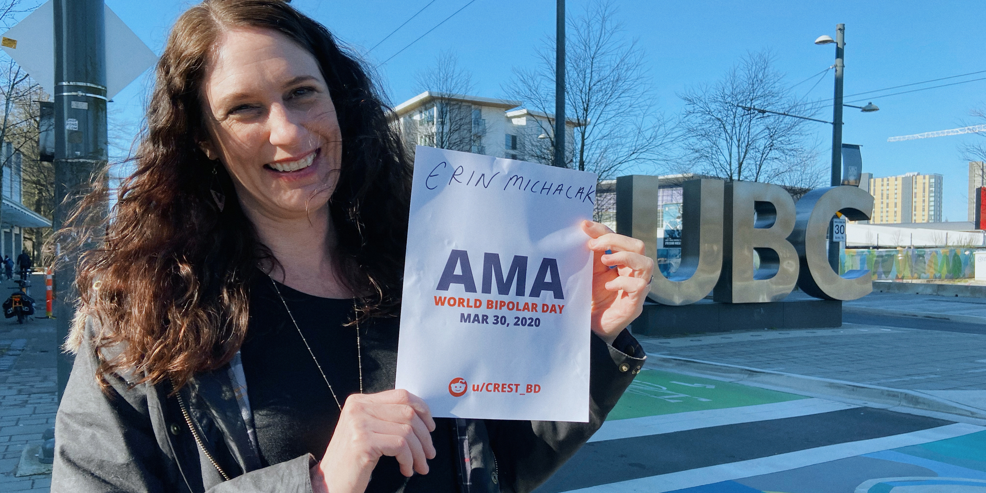 Erin outside, smiling and standing by a statue of the UBC logo. She is holding a sign proving she will be involved in the bipolar ama, with her name and the AMA date and time on it.