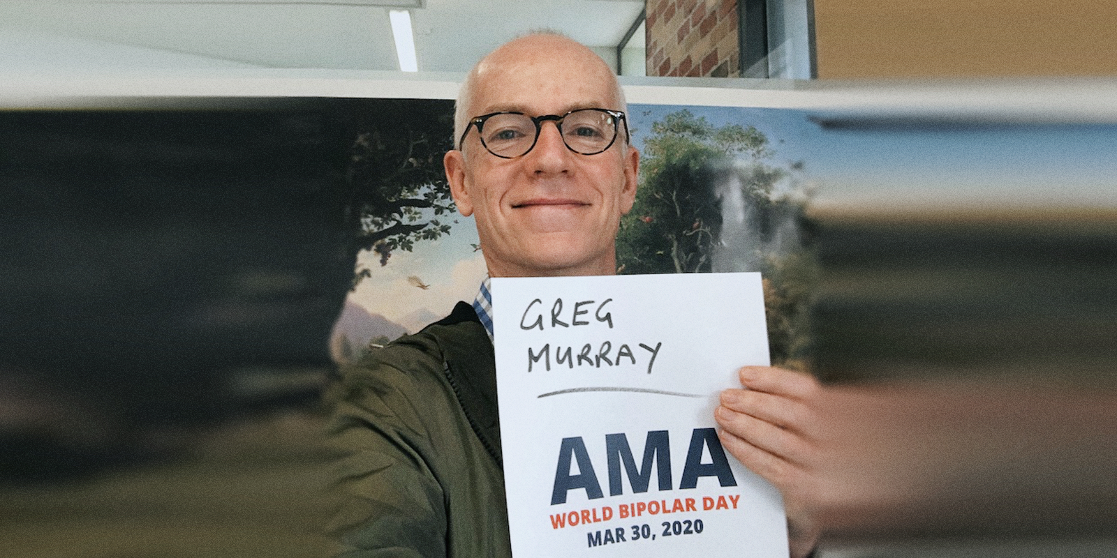 Greg sitting in an office, holding a sign proving he will be involved in the bipolar ama.