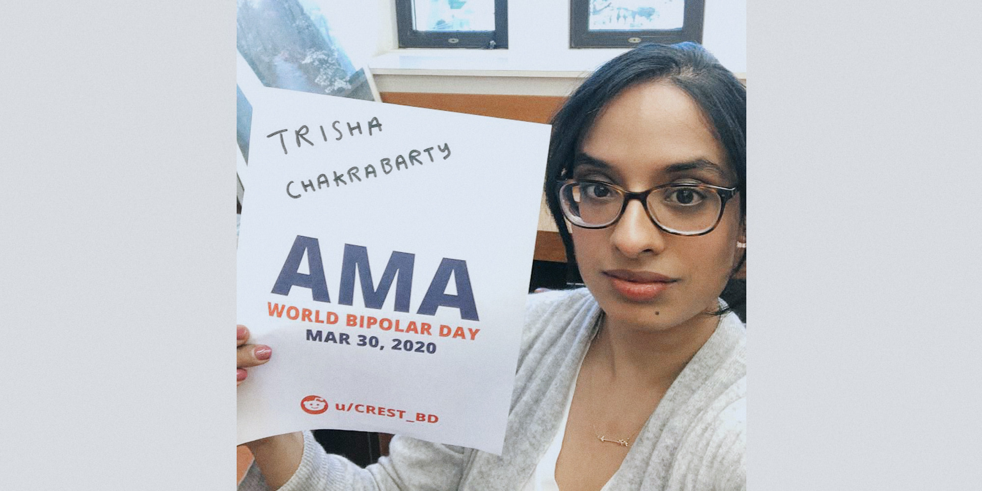 Trisha sitting in an office, looking upwards at the camera and holding a proof sign.