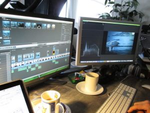 Two computer monitors with editor software on them, and two coffee cups on the desk.