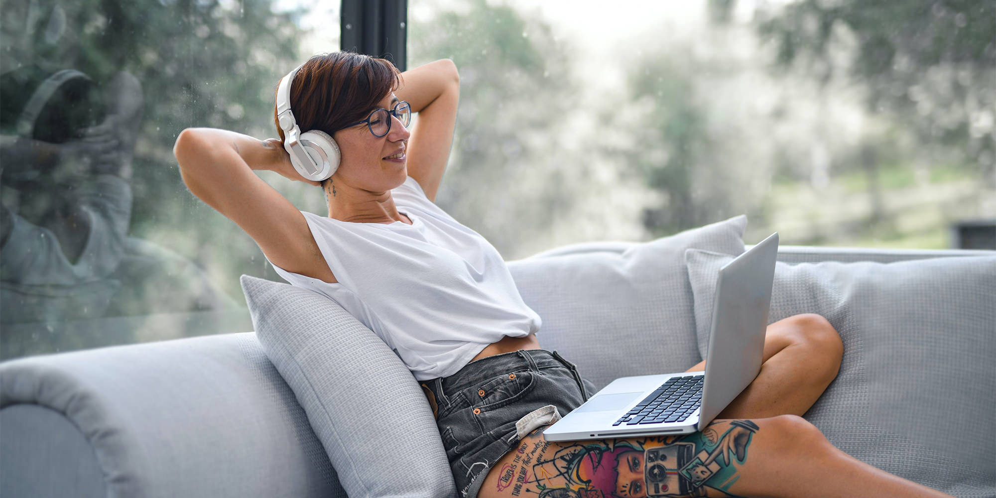 A woman in her late twenties with short hair and glasses, leaning back and listening to music on a white couch. Her eyes are closed and she looks relaxed - it's music self-care!