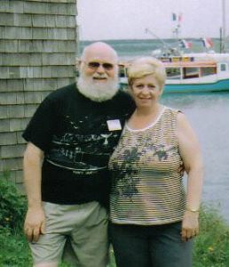 Raymond standing with his wife, Louise. They are outdoor near the water, and a boat can be seen in the background.