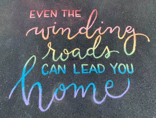 Chalk art done in rainbow colours on a road, saying 'Even the winding roads can lead you home,' reflecting Raymond's sentiments on aging well with bipolar.