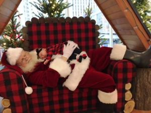 Raymond as Santa Clause! He's lying down on a black-and-red checked chair with a small baby sleeping on his chest.