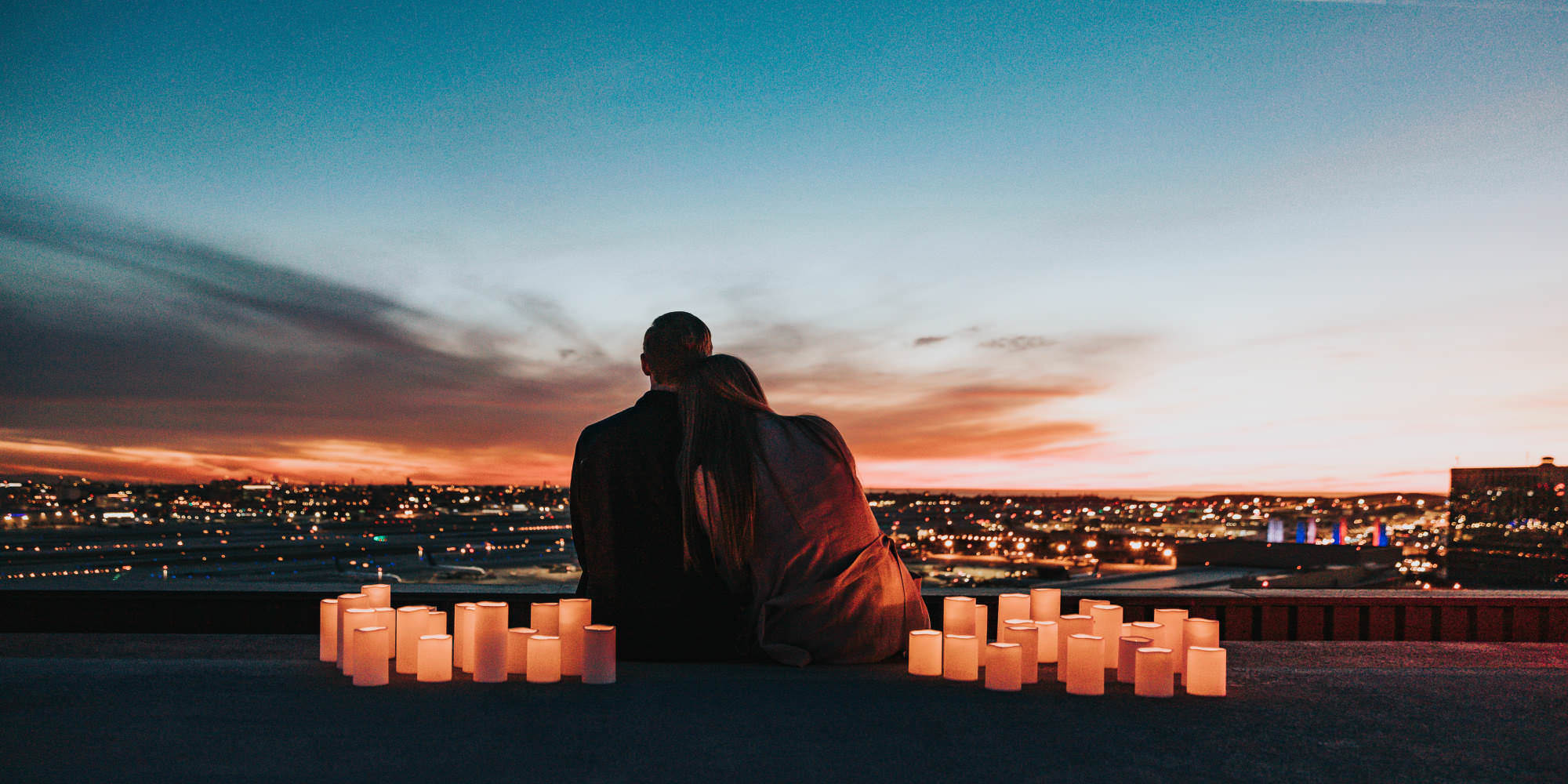 A silhouetted man and woman sit on a building rooftop at sunset. She is resting her head on his shoulder, and they are faced away from the camera, looking out over the city skyline. They are surrounded by large lit candles.