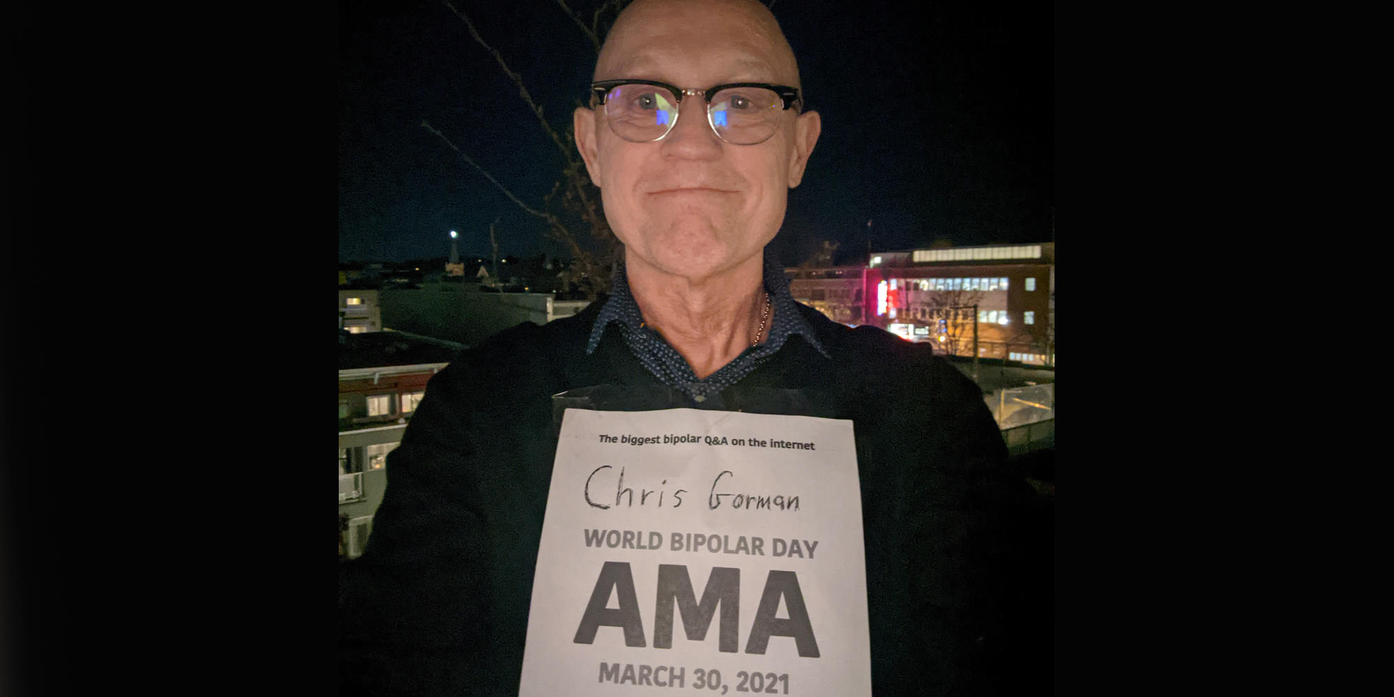 Chris is standing up outdoors at night, perhaps a higher-floor balcony. Buildings with lit windows are in the background. He is Caucasian and is bald and wearing horn-rimmed glasses and a dark sweater with a navy blue collar showing from his shirt underneath. He is holding the AMA proof sign.