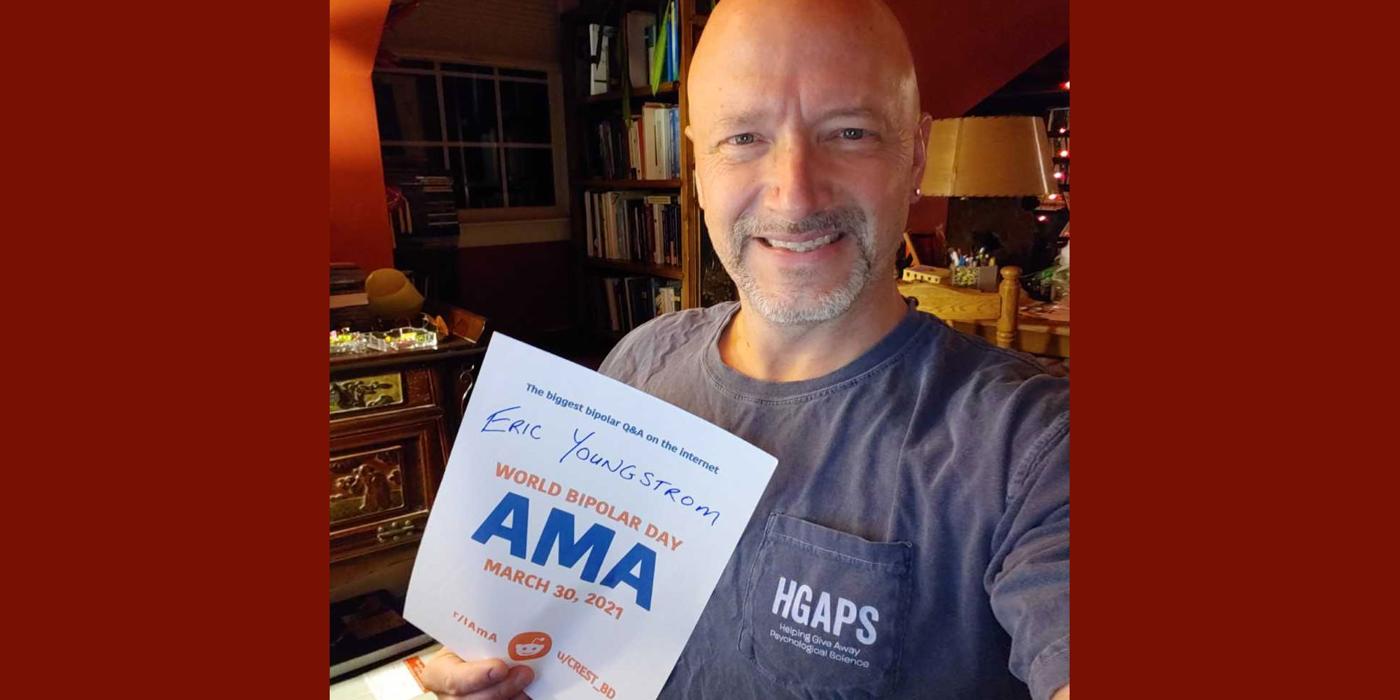 Eric is in a room in his home that looks like it might be an office, with reddish and white walls, dark-stained furniture, and a bookshelf. He is Caucasian and bald with a short greyish beard, and is wearing a grey shirt with HGAPS written on the pocket. He is holding the proof sign.