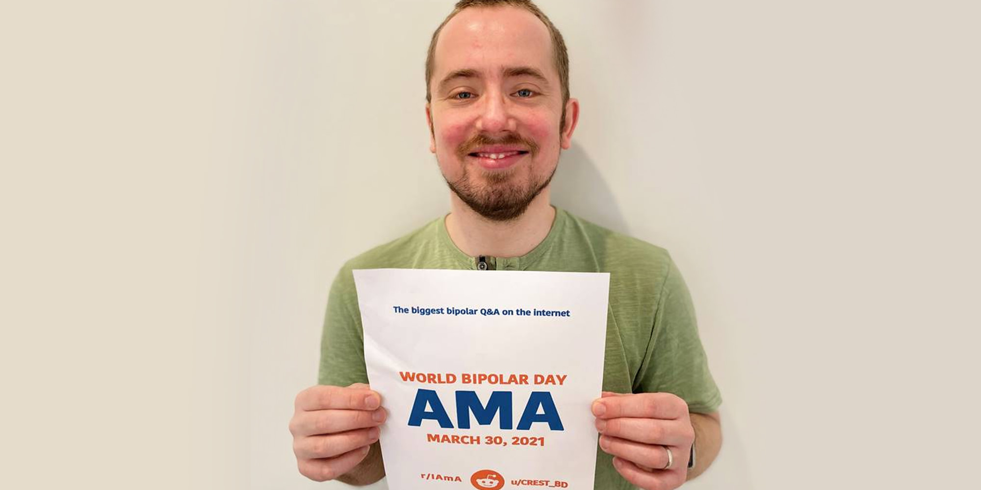 Thomas is standing in front of a beige walling holding up the AMA proof sign. He is Caucasian, with short, close-cropped brown hair and a slight beard. He is wearing a green t-shirt.