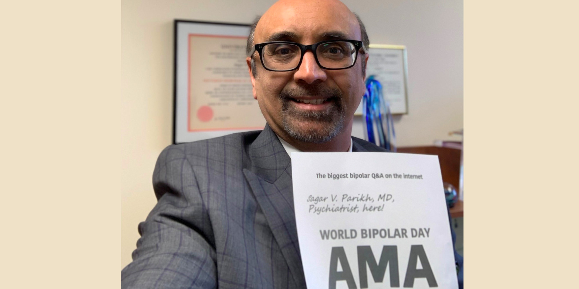 Sagar is in his office holding the AMA proof sign with his name written on it. He is Southeast Asian and is wearing a grey suit with a grid pattern and black, rectangular, thick-rimmed glasses.