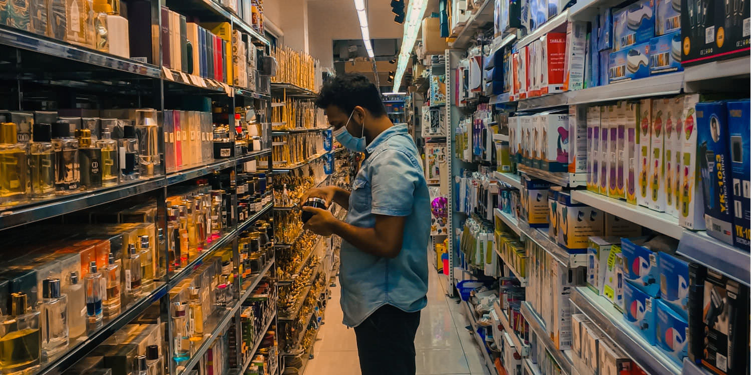 A young middle eastern man is standing in a aisle of a small grocery store. He is wearing a blue shirt and a medical mask and is inspecting what looks like a jar of jam.