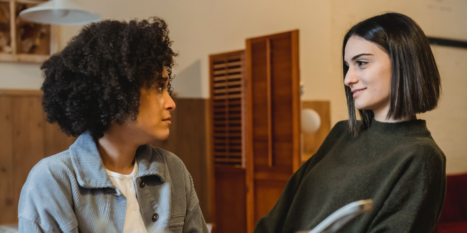 A young black woman is looking at her friend with a worried expression. She has curly black hair and is wearing a blue jacket. Her friend is possibly Latinx or Caucasian and is smiling encouragingly. She has a straight brown bob and a brown sweater on.